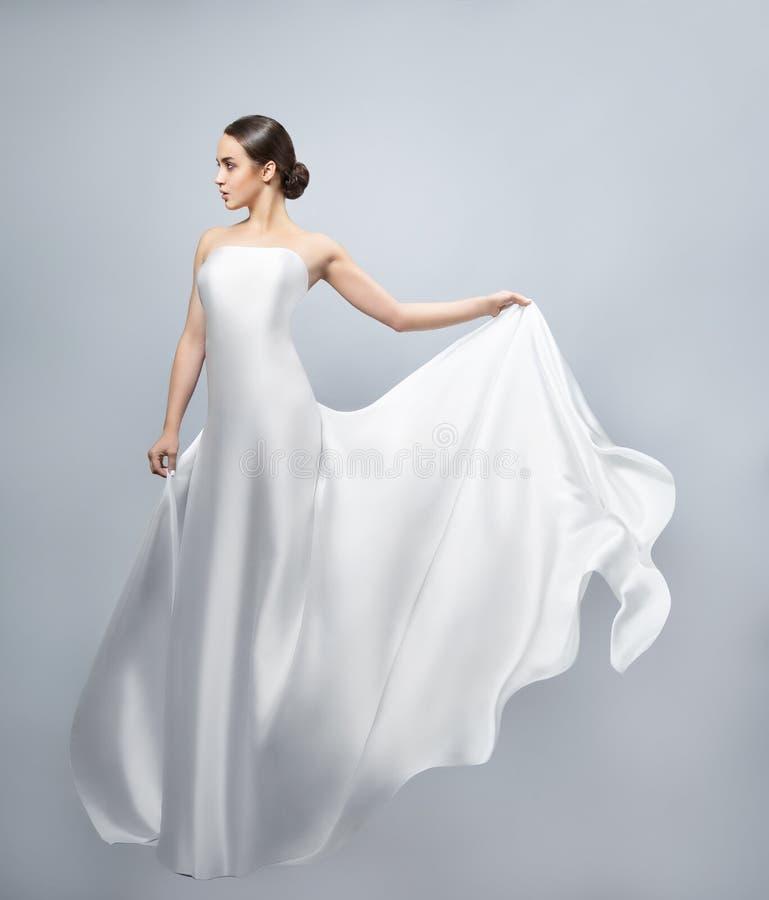 Modestående av en härlig kvinna i en vinkande vit klänning Ljust tyg flyger i vinden arkivbild