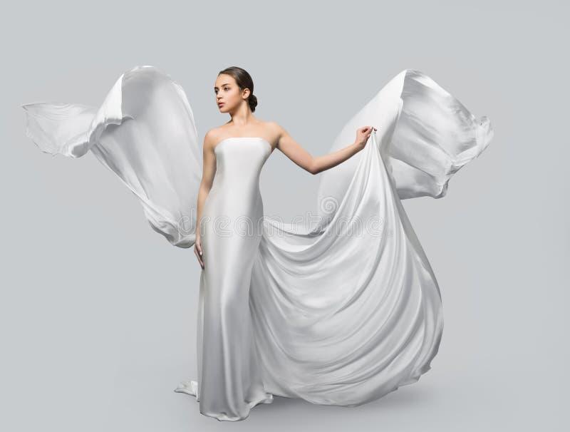 Modestående av en härlig kvinna i en vinkande vit klänning Ljust tyg flyger i vinden arkivfoton