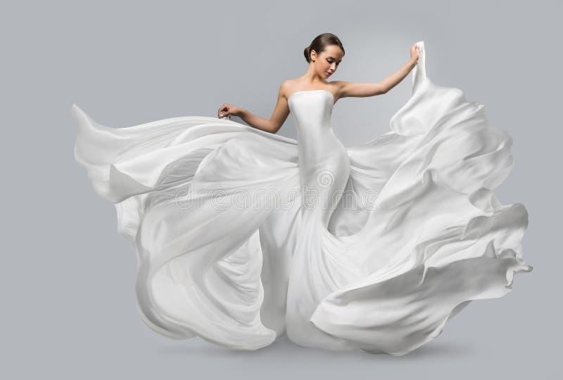 Modestående av en härlig kvinna i en vinkande vit klänning Ljust tyg flyger i vinden royaltyfri bild