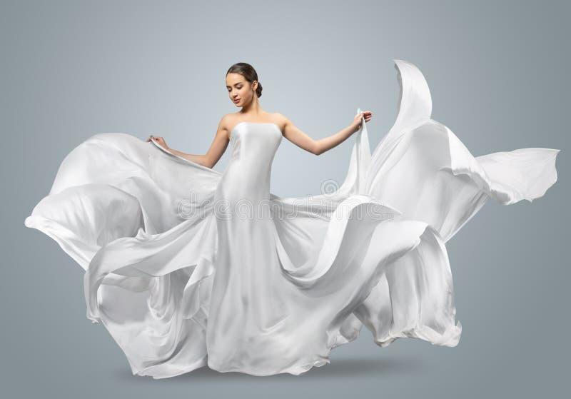 Modestående av en härlig kvinna i en vinkande vit klänning Ljust tyg flyger i vinden royaltyfri foto