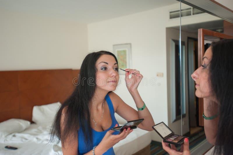 Modestående av en härlig ung flicka som gör smink nära spegeln Glamourdam i blått arkivfoton