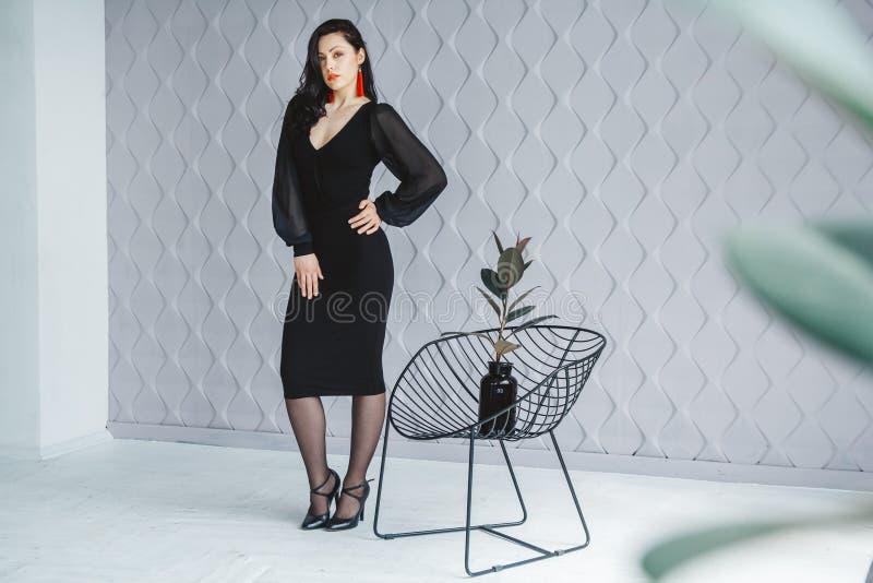 Modestående av en stilfull brunettflicka som bär en svart klänning Kvinna med långt hår som bär röda örhängen modell arkivbilder