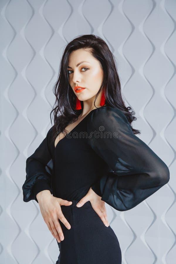 Modestående av en stilfull brunettflicka som bär en svart klänning Kvinna med långt hår som bär röda örhängen Posera in arkivfoton