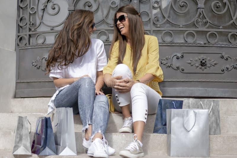 Modestående av unga härliga kvinnor med shoppingpåsar på royaltyfria bilder