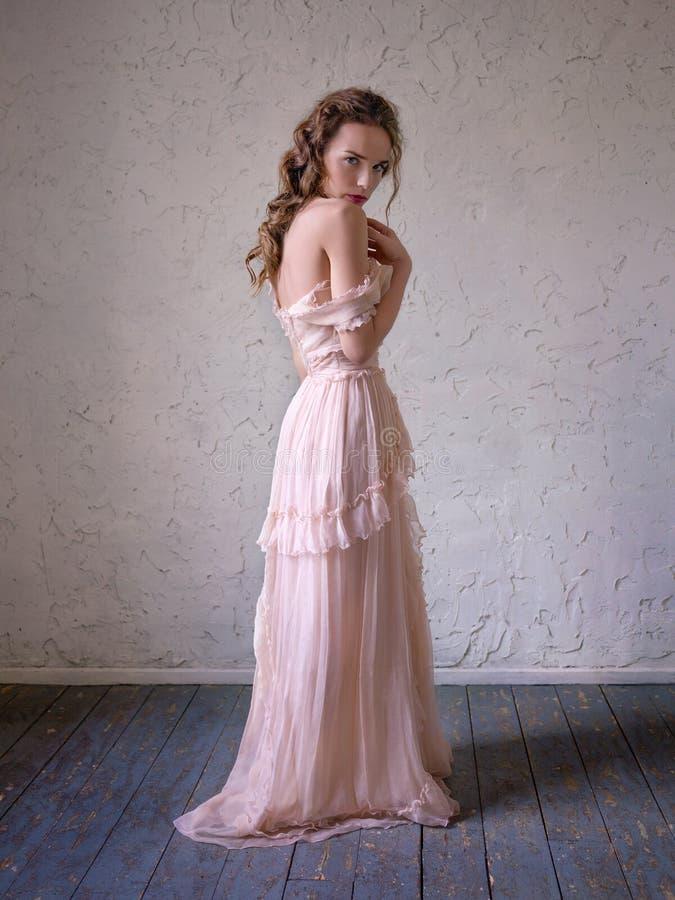 Modeståenden av den härliga kvinnan i en lång rosa färg klär arkivbilder