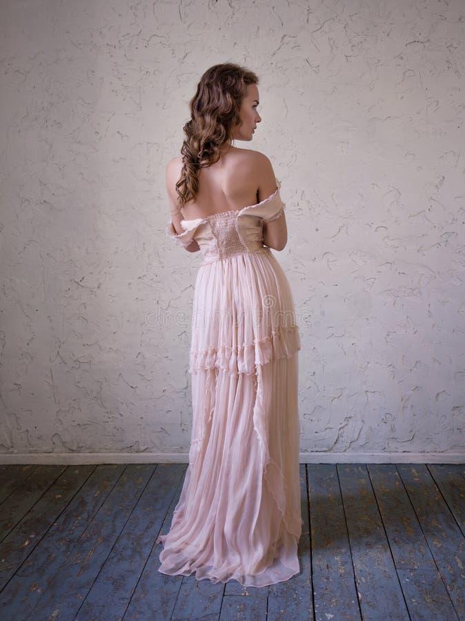 Modeståenden av den härliga kvinnan i en lång rosa färg klär royaltyfri fotografi