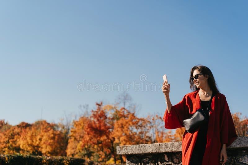 Modeståenden av den härliga kvinnan i höst parkerar arkivfoton