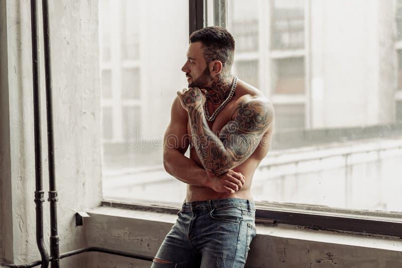 Modeståenden av den sexiga nakna manliga modellen med tatueringen och ett svart skägganseende i varmt poserar på nära fönstret Vi royaltyfri foto