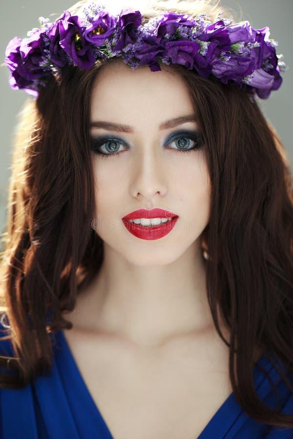 Modeståenden av en härlig brunettkvinna med att förbluffa utgör och kronan av purpurfärgade blommor i hennes huvud arkivbild