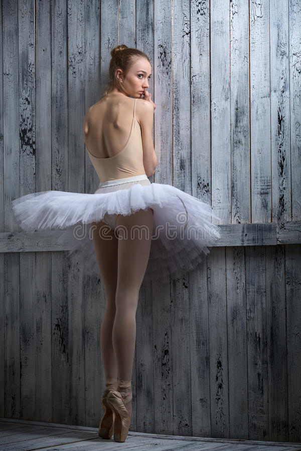 Modest ballerina standing near a wooden wall royalty free stock images