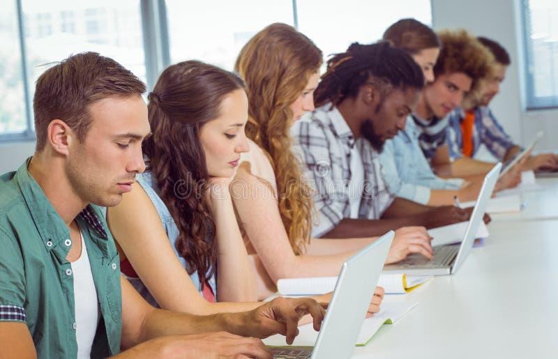Modestudenter som använder bärbara datorn fotografering för bildbyråer