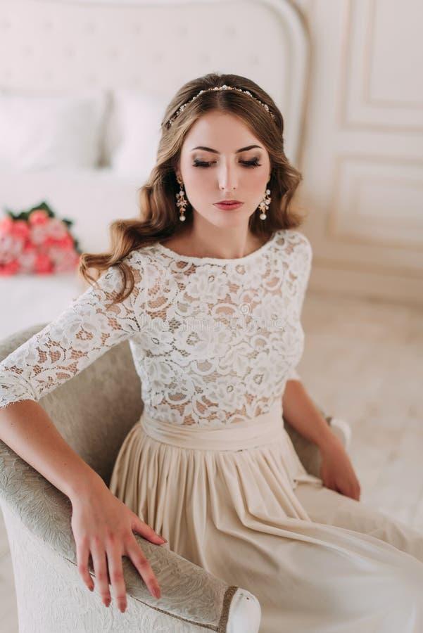 Modestudiofoto der sch?nen eleganten Braut mit dem dunklen Haar im luxuri?sen Heiratskleid mit Stirnband lizenzfreies stockfoto