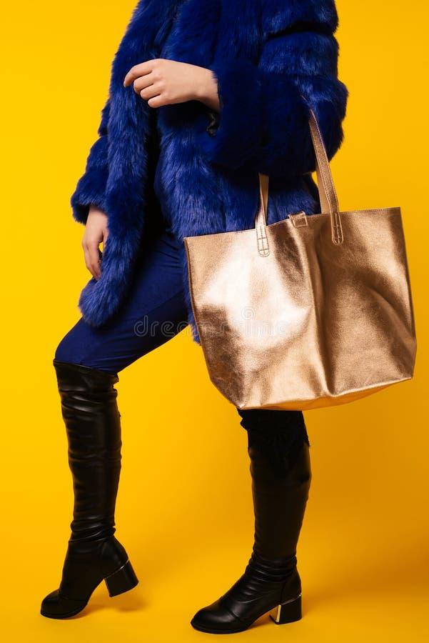 Modestudiofotoet av den ursnygga kvinnan bär det lyxiga blåa pälslaget, med den guld- påsen arkivfoto