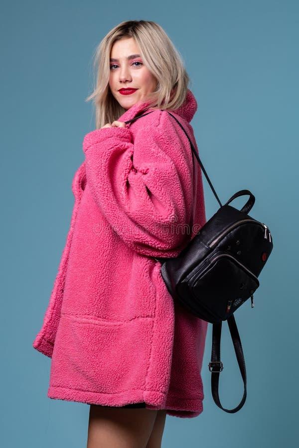 Modestudiostående av den blonda flickan med den svarta ryggsäcken royaltyfri foto