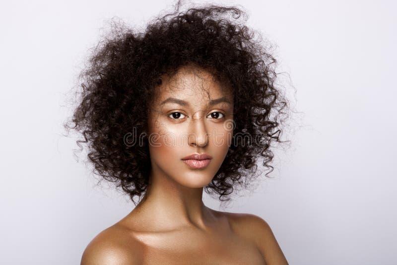 Modestudiostående av den härliga afrikansk amerikankvinnan med perfekt slät glödande mulatthud, smink arkivfoto