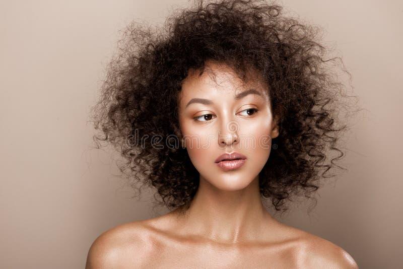 Modestudiostående av den härliga afrikansk amerikankvinnan med perfekt slät glödande mulatthud, smink arkivfoton