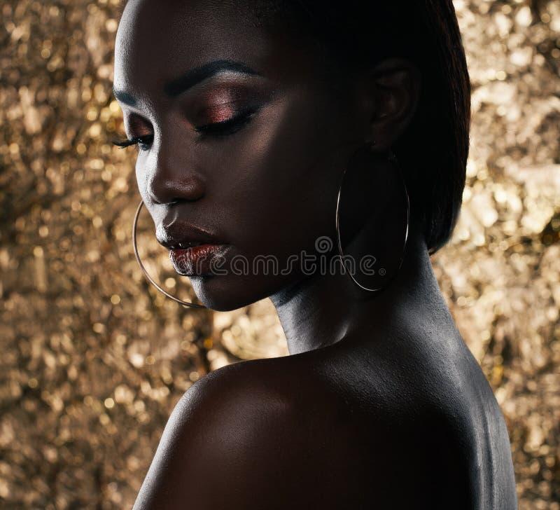Modestudiostående av en utöver det vanliga härlig afrikansk amerikanmodell med stängda ögon över guld- bakgrund royaltyfri fotografi