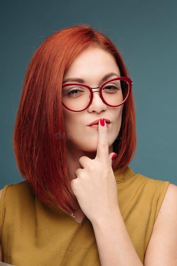 Modestudioståenden av den röda hårkvinnan för den nätta unga hipsteren med ljust sexigt utgör och exponeringsglas, att bära som ä royaltyfri bild