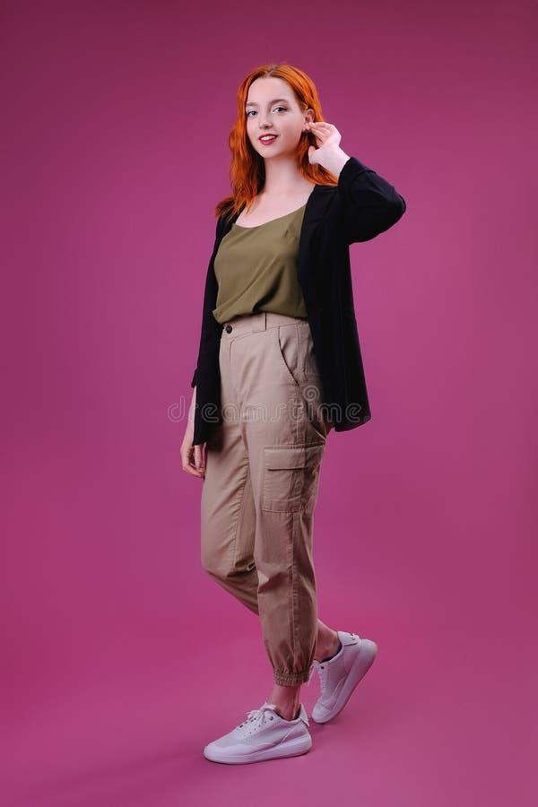 Modestudiost?ende av den unga kvinnan p? rosa bakgrund royaltyfria bilder