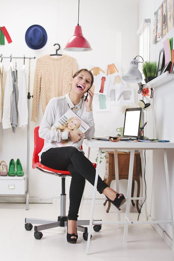 Modetidskriftredaktör i hennes kontor som talar med den smarta telefonen. royaltyfri bild