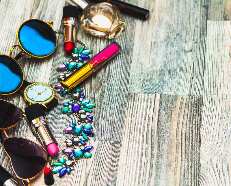 Modetillbehör: svart klocka, kantexponeringsglas och doft i svart kvinnlig kosmetolog skönhetsmedel nära avspeglar på vit royaltyfri bild