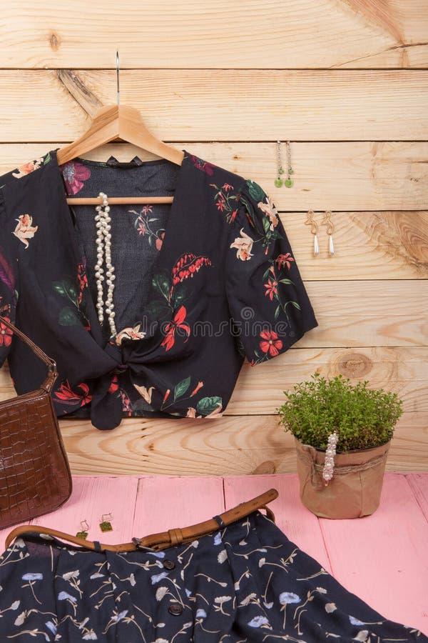 Modetrends - de zwarte de gewassenbovenkant/blouse in bloemendruk hangen op hanger, blauwe rok, riem, zak en juwelen: de klem van stock foto