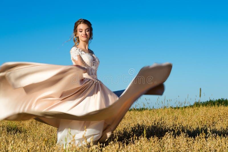 Modeung flicka i härlig klänning i fält arkivfoto