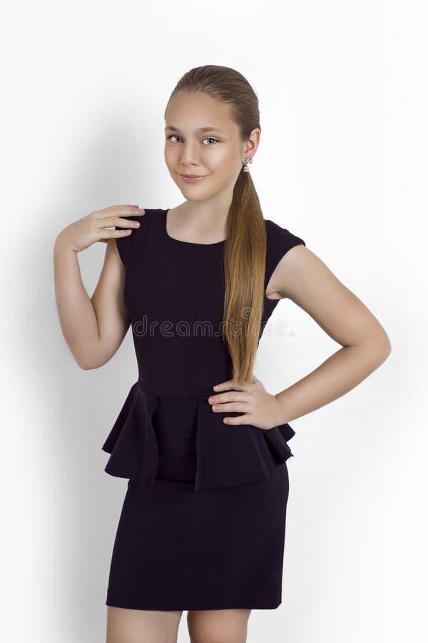 Modeung flicka, tonåringmodell i elegant klänning på en vit bakgrund i studiobilden royaltyfri bild