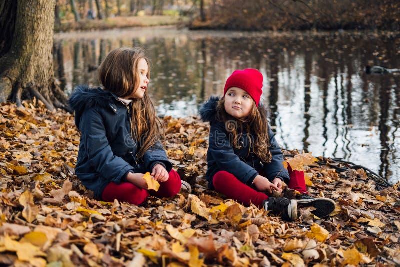Modeungar i höst parkerar Nära övre livsstilstående av två härliga caucasian flickor utomhus som in bär den gulliga moderiktiga d fotografering för bildbyråer