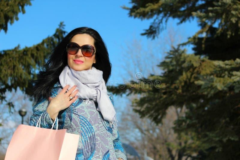 Modewinterfrau mit einer Einkaufstasche lizenzfreies stockfoto