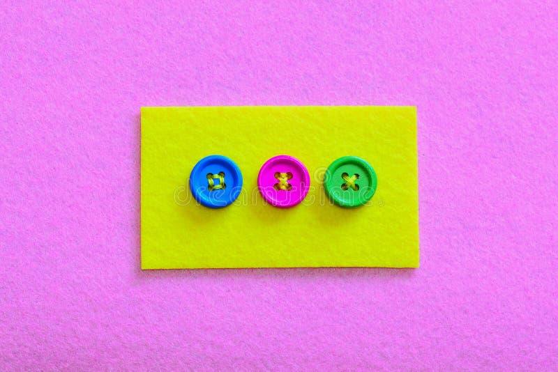 Modi semplici di cucire i bottoni a feltro Il giallo ha ritenuto il pezzo con i bottoni colourful isolati sul fondo del feltro di fotografie stock libere da diritti