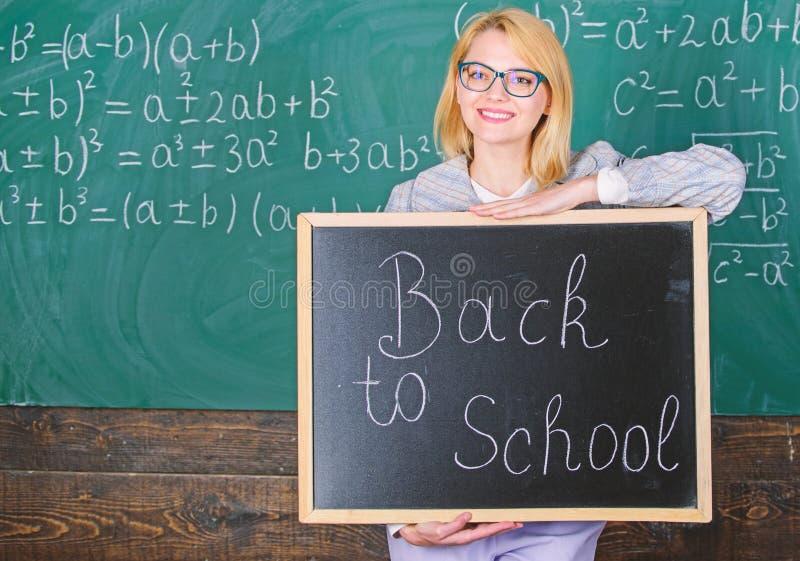 Modi superiori accogliere favorevolmente gli studenti di nuovo alla scuola Iscrizione della lavagna della tenuta della donna dell immagini stock