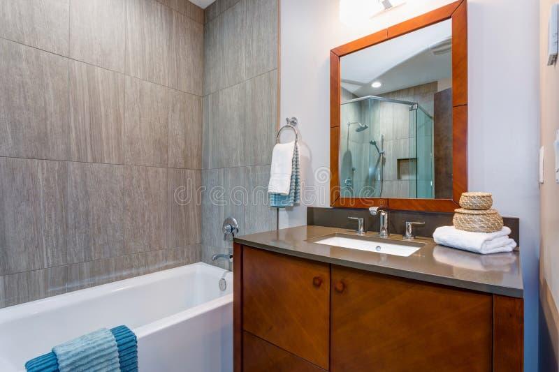 Modieus badkamersbinnenland met houten ijdelheidskabinet stock fotografie