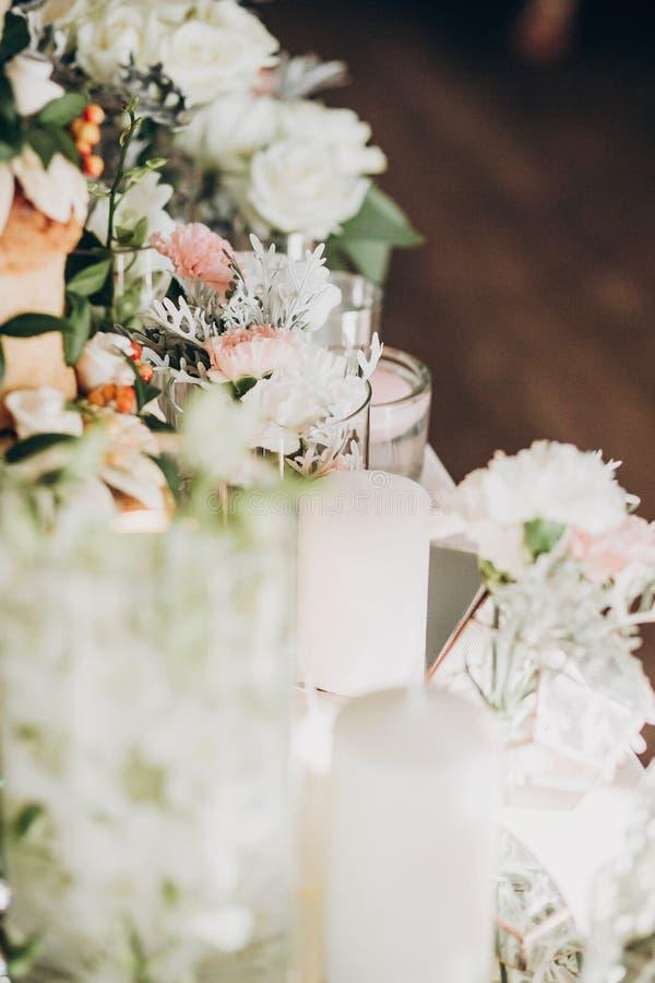Modieus bloemendecor op huwelijkslijst De witte rozen, eustoma, kaars, hydrangea hortensia bloeit in glas op huwelijksbelangrijks stock afbeeldingen