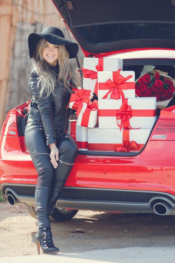 Modieus blonde dichtbij de auto met giftdozen stock afbeelding