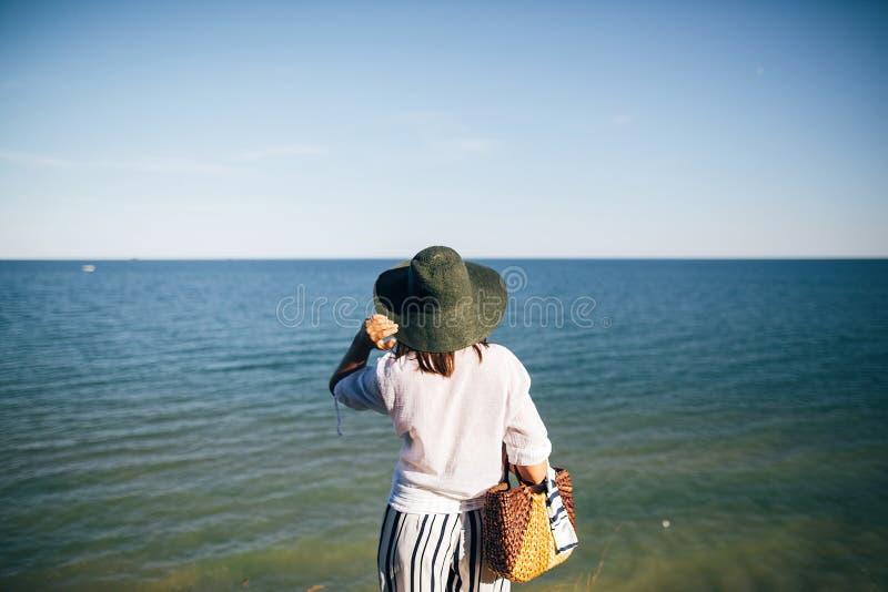 Modieus bohomeisje die in hoed op zee in zonnig avondlicht van zandige klip, achtermening kijken r stock afbeelding