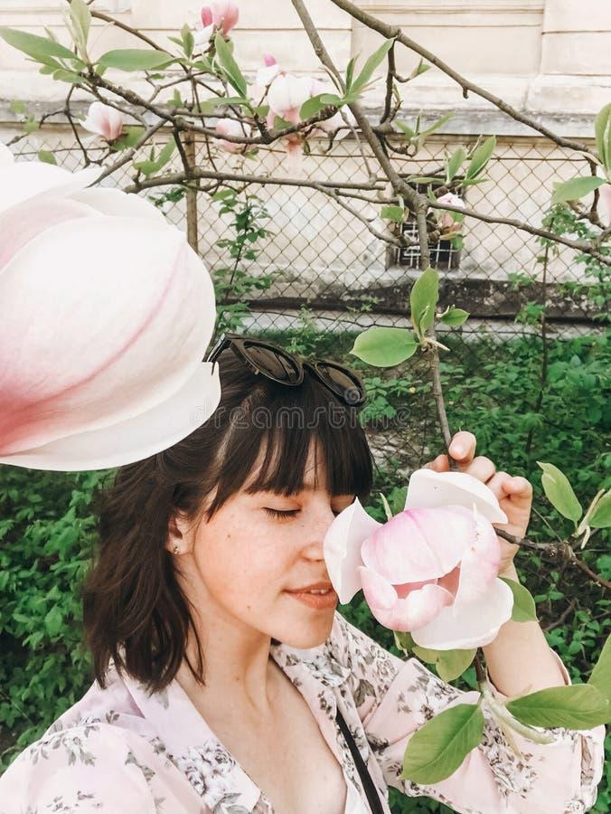Modieus bohomeisje die selfie met mooie roze magnoliabloemen maken op tak Hipstermeisje die en met magnolia ruiken stellen royalty-vrije stock foto's
