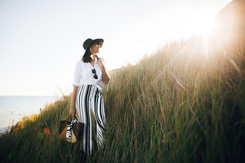 Modieus bohomeisje in hoed het stellen onder gras in zonnig avondlicht bij zandige klip dichtbij overzees Het gelukkige jonge mod stock afbeeldingen