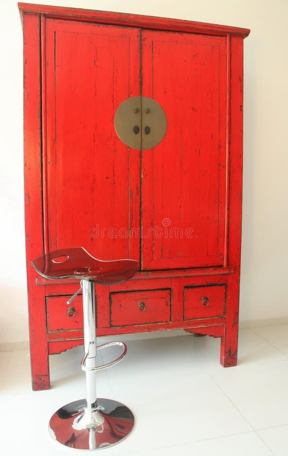 Modieus Chinees kabinet in rood en een moderne kruk stock afbeeldingen