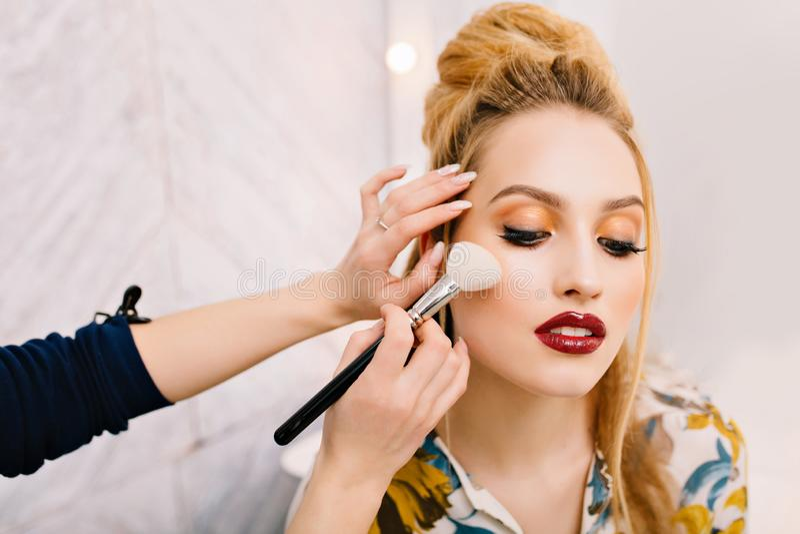 Modieus close-upportret van schitterende jonge vrouw die met mooi kapsel aan partij in kappersalon voorbereidingen treffen making stock foto