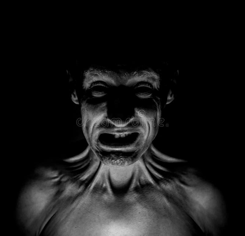 Modieus donker portret van de gevreesde volwassen Kaukasische mens die zijn gezicht rimpelt royalty-vrije stock foto's
