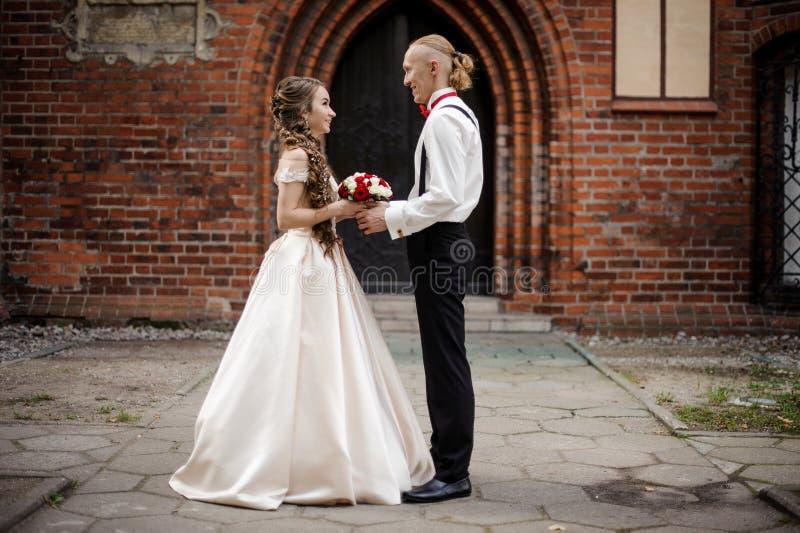Modieus echtpaar die en zich op de achtergrond van oude de bouwboog bevinden glimlachen royalty-vrije stock foto's