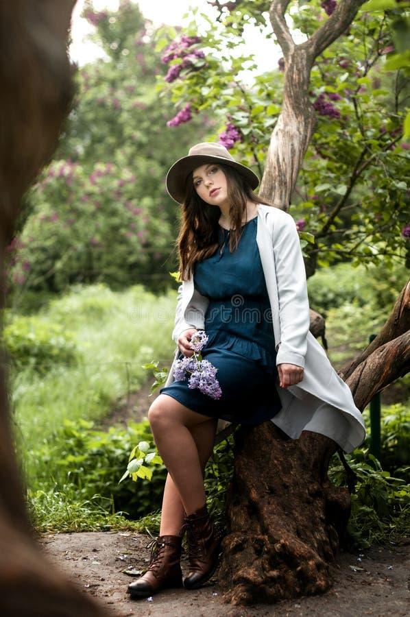 Modieus en charmant meisje in de tuin van sering stock fotografie