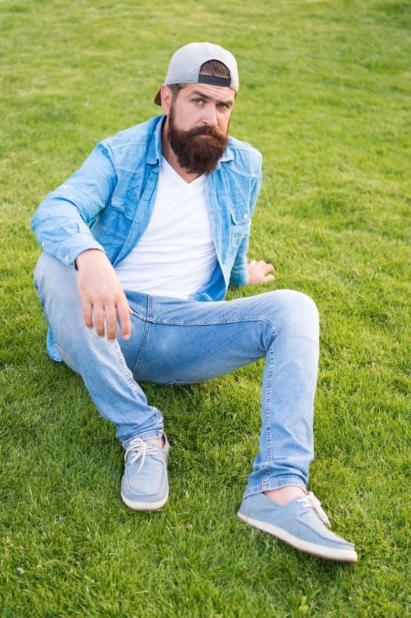 Modieus en comfortabel om te dragen Modieuze hipster in honkbalglb zitting op groen gras openlucht Het gebaarde mens dragen stock foto