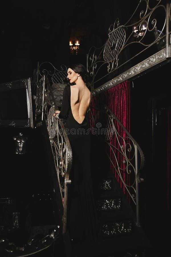 Modieus en sexy donkerbruin modelmeisje met perfect lichaam en rode lippen in zwarte avondjurk met het naakte achter stellen bij stock foto's