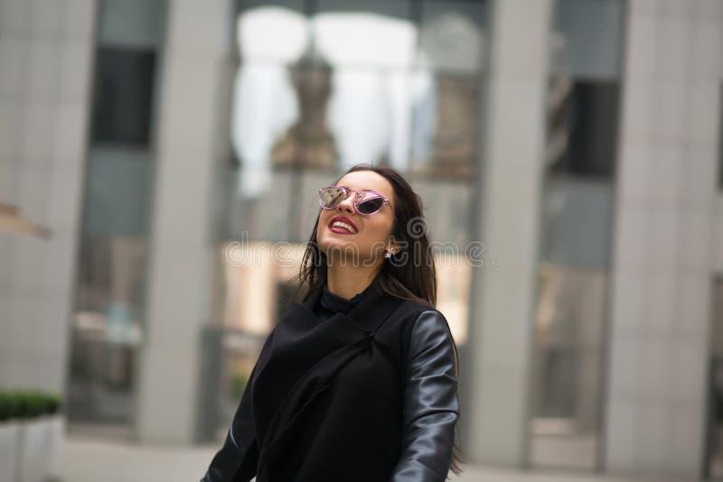 Modieus gekleed het glimlachen model met haar die in de windgang blazen stock fotografie