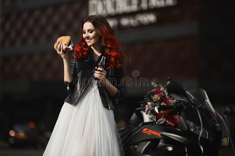 Modieus, gelukkig en glimlachend modelmeisje met rood haar en heldere make-up, in een witte huwelijkskleding en in een leer royalty-vrije stock foto's