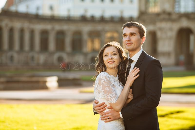Modieus gelukkig huwelijkspaar op het achtergrond mooie renaissance oude kasteel Romantische jonggehuwdebruidegom en bruid royalty-vrije stock afbeeldingen