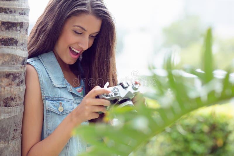 Modieus gelukkig meisje die haar camera bekijken royalty-vrije stock afbeeldingen