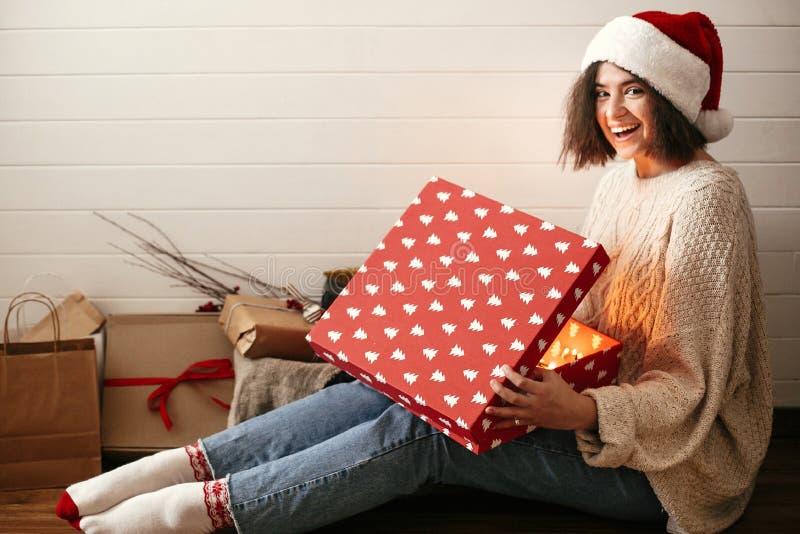 Modieus gelukkig meisje in santahoed het openen de doos van de Kerstmisgift met magisch licht Jonge hipstervrouw in het comfortab stock afbeelding